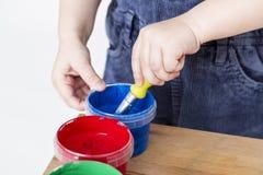 Cepillo de la tenencia del niño en tina de la pintura fotos de archivo libres de regalías
