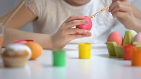 Cepillo de pintura de los huevos del color del niño, adornando el símbolo de Pascua, festival de la preparación metrajes