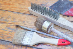 Cepillo de pintura tres, cepillo y raspador en el piso Imagen de archivo