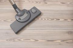 Cepillo del aspirador en un piso de madera fotografía de archivo libre de regalías