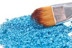 Cepillo del maquillaje con la sombra de ojos machacada azul Fotos de archivo