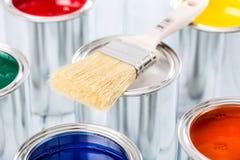 Cepillo del primer que miente en las latas multicoloras de la pintura fotos de archivo