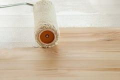 Cepillo del rodillo de pintura con la pintura blanca en fondo de madera Foto de archivo