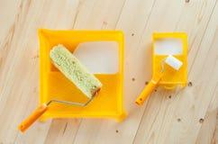 Cepillo del rodillo de pintura con la pintura blanca en fondo de madera Fotografía de archivo