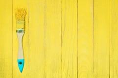 Cepillo en pintura amarilla en fondo de madera azul y amarillo Imagen de archivo libre de regalías