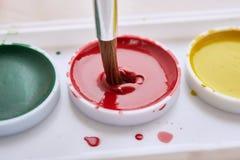 Cepillo en pintura roja Fotografía de archivo