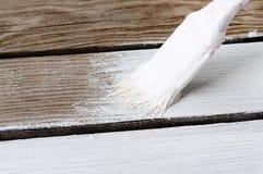 Cepillo en un fondo de madera con la pintura blanca Fotos de archivo libres de regalías