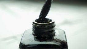 Cepillo femenino de las clavadas de la mano en un tarro de tinta para el cierre de dibujo para arriba Brochas pasadas de moda chi Fotografía de archivo libre de regalías