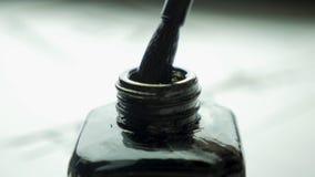 Cepillo femenino de las clavadas de la mano en un tarro de tinta para el cierre de dibujo para arriba Brochas pasadas de moda chi Fotos de archivo