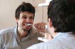 Cepillo loco del hombre sus dientes, miradas en su reflexión en el espejo foto de archivo libre de regalías