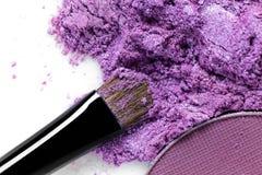 Cepillo púrpura machacado de la sombra de ojos y del maquillaje en el fondo blanco Imagen de archivo