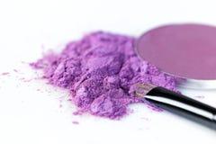 Cepillo púrpura machacado de la sombra de ojos y del maquillaje en el fondo blanco Foto de archivo
