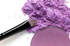 Cepillo púrpura machacado de la sombra de ojos y del maquillaje en el fondo blanco Imagen de archivo libre de regalías
