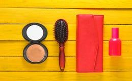 Cepillo para el pelo, espejo, monedero, botella de perfume Accesorios de la tendencia en un fondo de madera amarillo Imagen de archivo libre de regalías