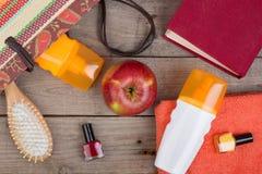 cepillo para el pelo, toalla anaranjada, crema del sol, loción, bolso de la playa, esmalte de uñas, un libro en un fondo de mader Fotografía de archivo