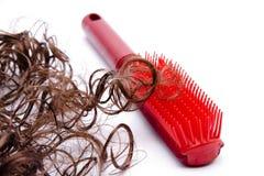 Cepillo para el pelo y pelo plásticos rojos Imagen de archivo libre de regalías