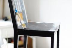 Cepillo para pintar la mentira en una silla en el cuarto Imagen de archivo