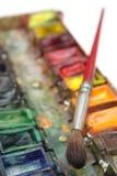 Cepillo y caja de pinturas Fotos de archivo libres de regalías