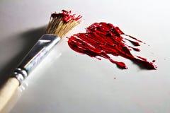 Cepillo y corazón pinted del color rojo Imagen de archivo