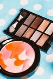 Cepillo y cosméticos del maquillaje en la tabla de madera azul Fotografía de archivo