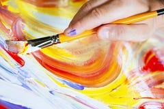 Cepillo y pintura de la tenencia de la mano con las pinturas acrílicas Imagen de archivo