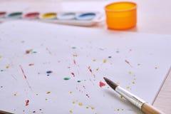 Cepillo y pintura en la página blanca Fotos de archivo