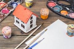 Cepillo y pintura en una tabla Imagen de archivo libre de regalías