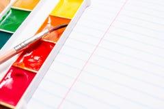 Cepillo y pinturas coloreadas brillantes de la acuarela papel Fotos de archivo