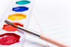 Cepillo y pinturas coloreadas brillantes de la acuarela papel Foto de archivo