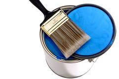 Cepillo y tapa de pintura en una poder de pintura azul Imagenes de archivo