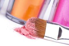 Cepillo y tubos del maquillaje con sombreadores de ojos Fotos de archivo