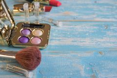 Cepillo y un sistema de cosméticos del ` s de las mujeres en una tabla de madera azul Imagen de archivo
