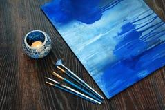 Cepillo y vela azules de pintura en palmatoria Fotografía de archivo libre de regalías
