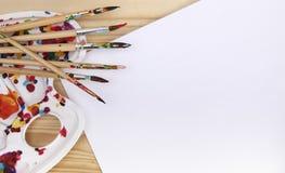 Cepillos artísticos, caballete, documento sobre la mesa en el estudio del ` s del artista Foto de archivo