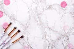 Cepillos cosméticos con las decoraciones rosadas en un fondo de mármol imágenes de archivo libres de regalías