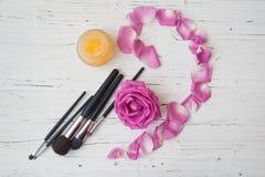 Cepillos, crema amarilla y rosa del rosa en la tabla de madera blanca Imagen de archivo libre de regalías