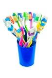 Cepillos de dientes coloridos en una taza azul Fotografía de archivo