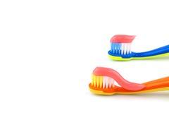 Cepillos de dientes del color con crema dental rosada Foto de archivo
