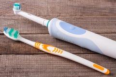 Cepillos de dientes eléctricos y manuales en el fondo de madera Imágenes de archivo libres de regalías