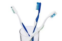 Cepillos de dientes en un vidrio, aislado en blanco Fotografía de archivo libre de regalías