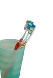 Cepillos de dientes en un vidrio verde Imagen de archivo