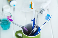 Cepillos de dientes en vidrio en la tabla Imagen de archivo