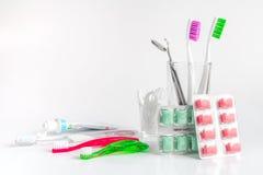 Cepillos de dientes en vidrio en las herramientas blancas del fondo para el cuidado oral Imágenes de archivo libres de regalías
