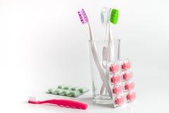 Cepillos de dientes en vidrio en las herramientas blancas del fondo para el cuidado oral Fotografía de archivo