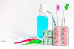 Cepillos de dientes en vidrio en las herramientas blancas del fondo para el cuidado oral Fotos de archivo