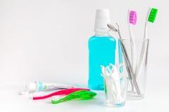 Cepillos de dientes en vidrio en las herramientas blancas del fondo para el cuidado oral Foto de archivo libre de regalías