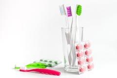 Cepillos de dientes en vidrio en las herramientas blancas del fondo para el cuidado oral Imagen de archivo