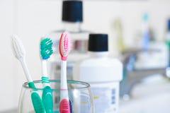 Cepillos de dientes en vidrio en la tabla en cuarto de baño Imagen de archivo