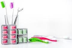 Cepillos de dientes en vidrio en las herramientas blancas del fondo para el cuidado oral Imagenes de archivo