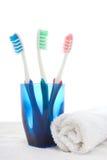 Cepillos de dientes en vidrio y toalla azules Fotografía de archivo libre de regalías